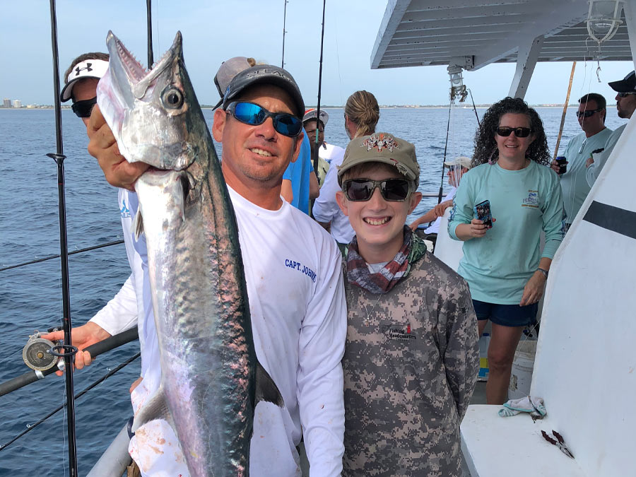 kid and fishing guide holding a large kingfish