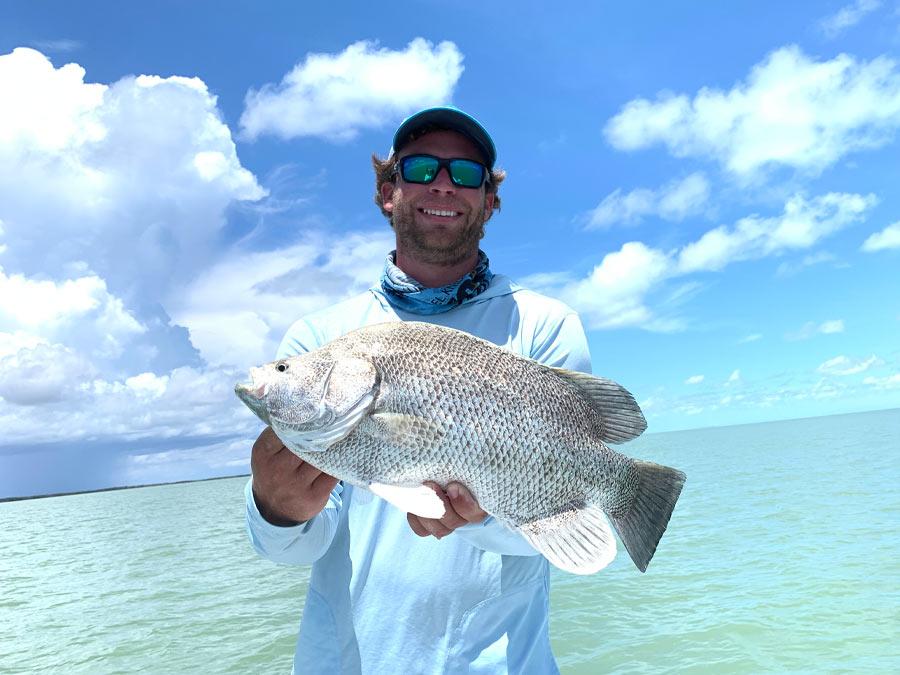 fisherman holding tripletail